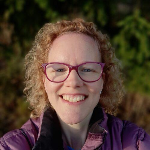 Leende kvinna med röda glasögon